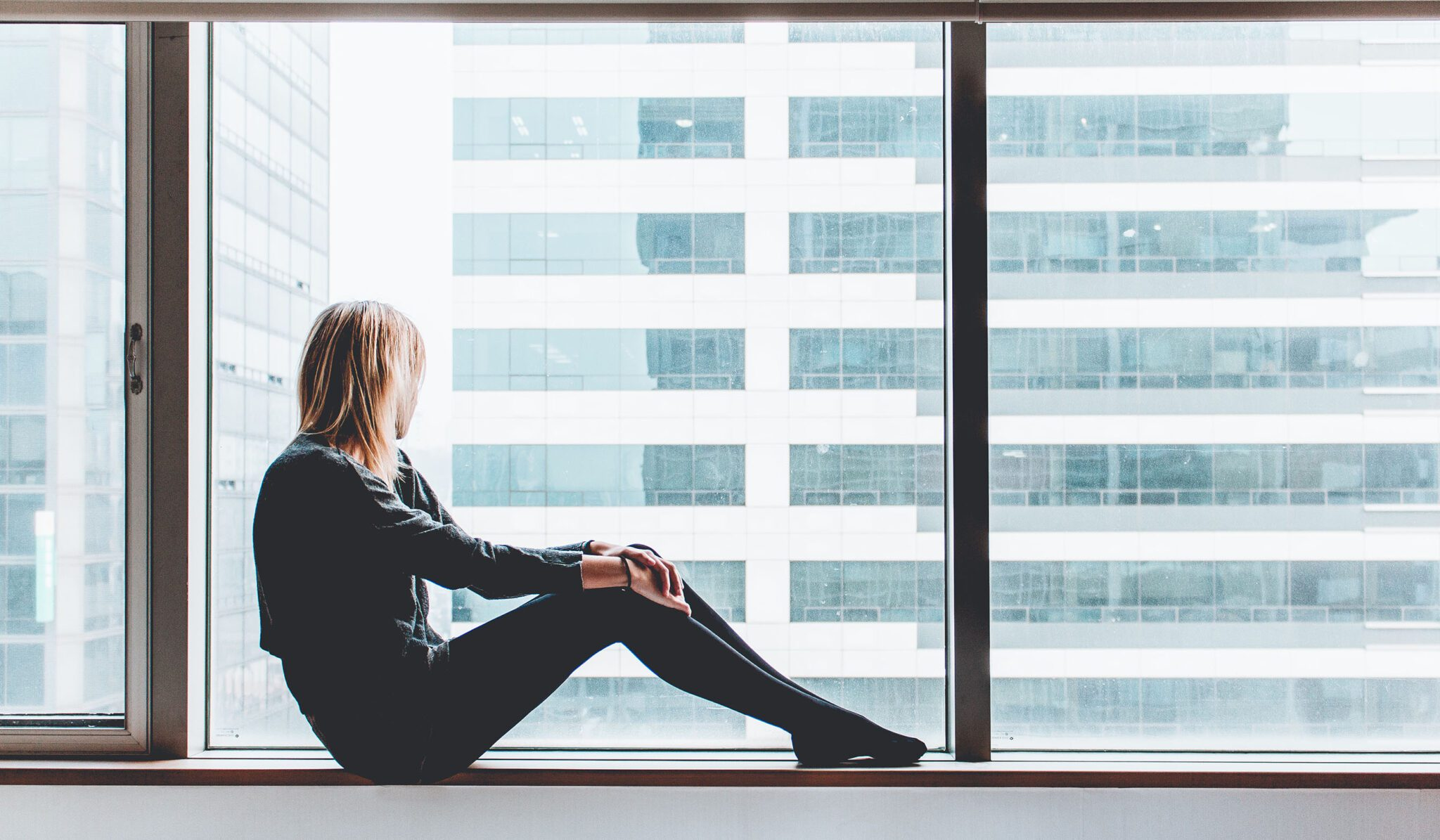 woman considering an at-home fertility test while staring out the window